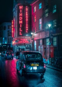 The Windmill Theatre at night in London. A London Taxi and neon lights. Urban photography
